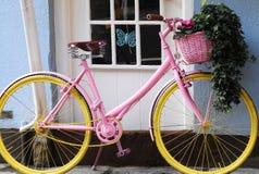 美丽的桃红色和黄色自行车在英国村庄停放了 免版税库存照片