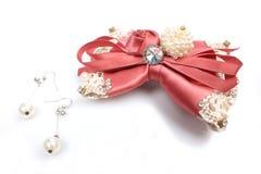 美丽的桃红色弓和珍珠耳环 免版税库存照片