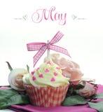 美丽的桃红色心脏或母亲节题材杯形蛋糕与季节性花和装饰5月 库存图片