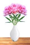 美丽的桃红色牡丹在桌上的白色花瓶开花 免版税库存照片