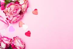 美丽的桃红色玫瑰、装饰五彩纸屑心脏和桃红色丝带在桃红色情人节背景 库存照片