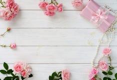 美丽的桃红色玫瑰和礼物花束在桃红色包装在白色木背景 顶视图 复制空间 库存图片