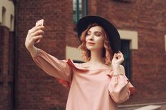 美丽的桃红色礼服和黑帽会议的女孩 有桃红色卷发旅行的女孩 女孩在智能手机做一张照片 免版税库存图片