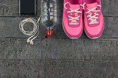 美丽的桃红色运动鞋、耳机、水和苹果在一个木黑暗的地板上 在视图之上 免版税库存照片