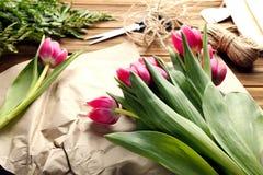 美丽的桃红色郁金香、纸、剪刀和亚麻制串在woode 免版税库存照片