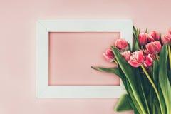 美丽的桃红色郁金香开花与绿色叶子并且倒空白色框架 免版税库存图片
