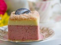 美丽的桃红色酸奶蛋糕和一杯茶 免版税库存照片