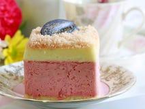 美丽的桃红色酸奶蛋糕和一杯茶 免版税库存图片