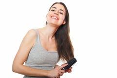 美丽的梳的女性头发她的年轻人 免版税库存照片