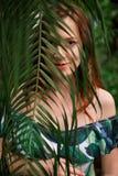 美丽的棕榈叶的年轻人怀孕的白种人红头发人妇女 免版税库存照片