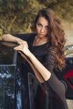 美丽的棕色黑礼服摆在的头发少妇 免版税库存照片