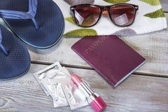 美丽的概念池假期妇女年轻人 夏天与太阳镜,拖鞋,护照,避孕套,拷贝空间的海滩背景 库存图片