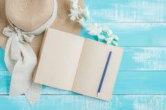 美丽的概念池假期妇女年轻人 被打开的书、在蓝色木桌上的堆毛巾和帽子 库存照片