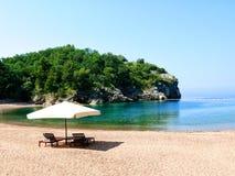 美丽的概念池假期妇女年轻人 两把椅子在含沙b的一把白色伞下 库存图片