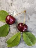 美丽的樱桃在桌上和在茶碟 樱桃和樱桃核,在板材挖坑 免版税库存照片