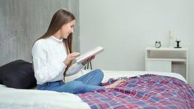 美丽的欧洲年轻女人坐拿着读的床有趣的书 股票录像