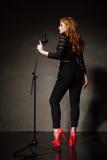 美丽的歌手画象红色脚跟和黑衣裳的 免版税库存照片