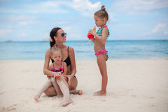 美丽的母亲和两她的在异乎寻常的海滩的孩子 库存图片