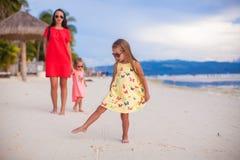 美丽的母亲和两她的在异乎寻常的海滩的孩子 免版税库存图片
