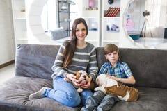 美丽的母亲和儿子收留英国牛头犬小狗 库存图片