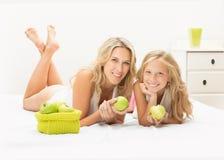 美丽的母亲和女儿与苹果一起 免版税图库摄影
