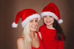 美丽的母亲和女儿有圣诞老人帽子的 库存图片