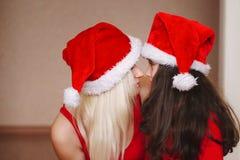 美丽的母亲和女儿有圣诞老人帽子的 免版税库存照片