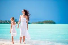 美丽的母亲和她可爱的矮小的女儿海滩的 库存图片
