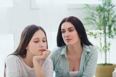 美丽的母亲和她逗人喜爱的女儿讨论少年问题 库存照片