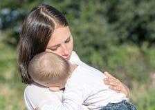 年轻美丽的母亲和拥抱在自然的男婴在夏天 拿着睡觉儿童离子的俏丽的妇女她的胳膊 免版税库存照片