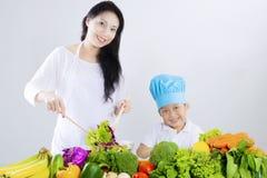 美丽的母亲和男孩做沙拉 免版税库存图片