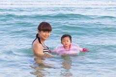 美丽的母亲和逗人喜爱的享用在海的女婴 库存照片