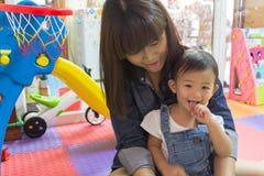 美丽的母亲和逗人喜爱的享用在玩具屋子里的女婴 免版税库存图片