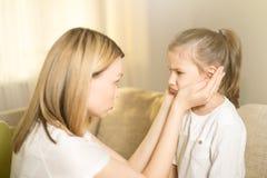 美丽的母亲安慰他的年轻沮丧的女儿 免版税库存图片