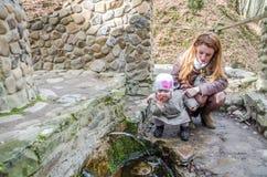 美丽的母亲用她的从从在植被中的岩石流动的圣洁春天的女儿婴孩饮料水 库存图片