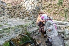美丽的母亲用她的从从在植被中的岩石流动的圣洁春天的女儿婴孩饮料水 免版税图库摄影
