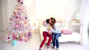 美丽的母亲的照料儿子的迷人的孩子和惊奇在有欢乐圣诞树的明亮的卧室和 影视素材
