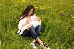 美丽的母亲获得与她的小逗人喜爱的婴孩的乐趣在夏天庭院 库存照片