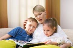 美丽的母亲读一本书给她的幼儿 姐妹和兄弟听故事 免版税库存照片