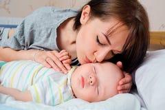 美丽的母亲画象有她的7个月的婴孩睡觉 库存图片