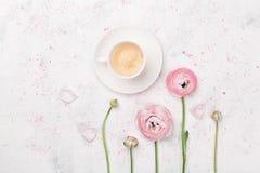 美丽的毛茛属花和咖啡在白色桌上的从上面 在淡色的早餐 平的位置样式 免版税图库摄影