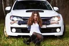 美丽的汽车女孩炫耀时髦的白色 库存照片