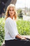 年轻美丽的沉思白肤金发的女孩坐长凳在公园 库存图片