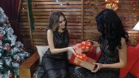美丽的浅黑肤色的男人和金发碧眼的女人有长的头发的在给礼物的性感的黑色礼服圣诞节或新年 库存图片