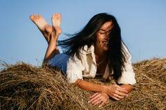 美丽的浅黑肤色的男人在干草堆,秋天说谎 免版税库存照片