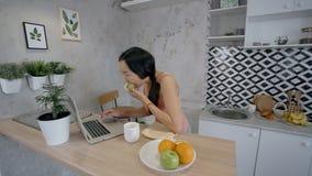 美丽的浅黑肤色的男人看膝上型计算机屏幕,吃坐在家庭内部的苹果 影视素材