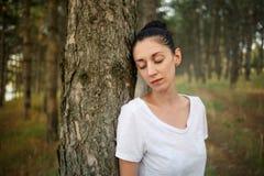 美丽的浅黑肤色的男人倾斜了反对杉树并且闭上了他的眼睛 库存图片