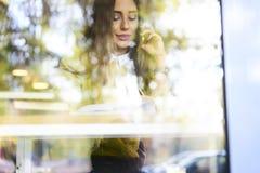 美丽的浅黑肤色的男人在一次黄色女衬衫会议和飞机的售票票,当坐在咖啡馆时 图库摄影