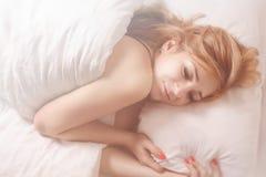 美丽的浪漫妇女在早晨床上 免版税库存图片