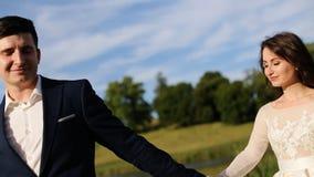 美丽的浪漫拥抱在日落的老城堡附近的婚礼夫妇、新郎和新娘 股票视频